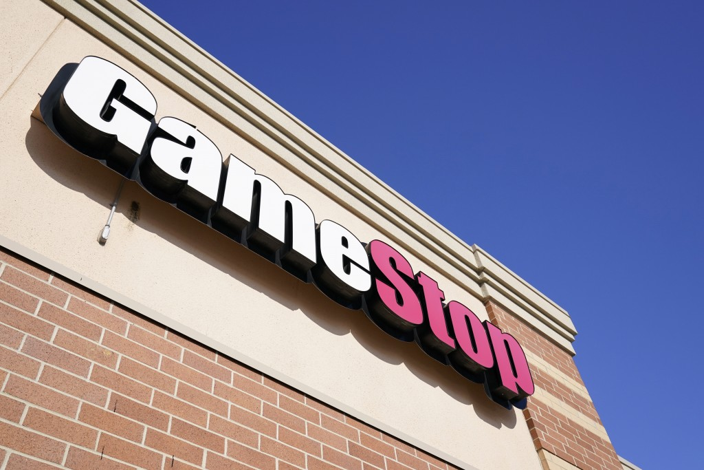 FILE - In this Thursday, Jan. 28, 2021, file photo, a GameStop sign is seen above a store, in Urbandale, Iowa. GameStop says it's nominating Chewy fou...