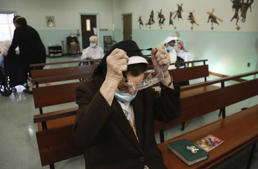 Sister Mary Carol Kardell, of the Felician Sisters of North America, puts on goggles after morning Mass at St. Anne Home in Greensburg, Pa., on Thursd...