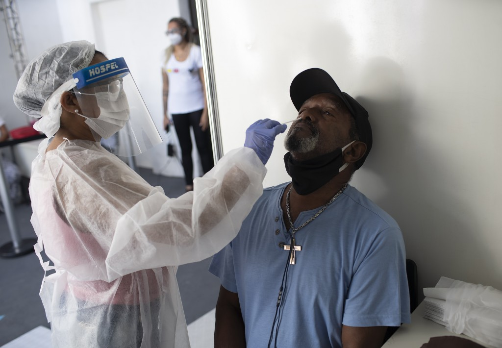 A health worker collects a nasal swab sample for a COVID-19 test in the Mare Complex favela of Rio de Janeiro, Brazil, Thursday, April 8, 2021. (AP Ph...