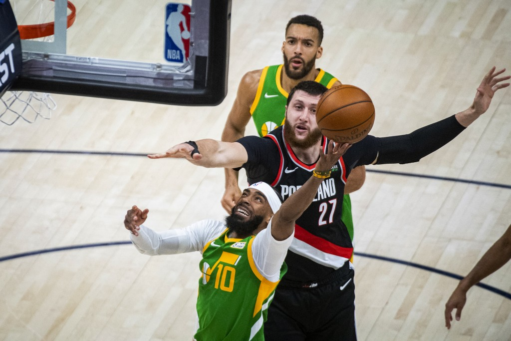 Utah Jazz guard Mike Conley (10) lays the ball up while guarded by Portland Trail Blazers center Jusuf Nurkic (27) during the first half of an NBA bas...