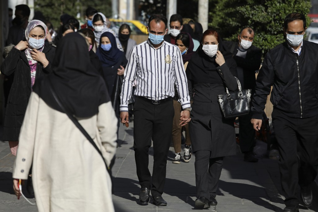 FILE - In this April 5, 2021, file photo, people wearing protective face masks to help prevent the spread of the coronavirus walk in downtown Tehran, ...