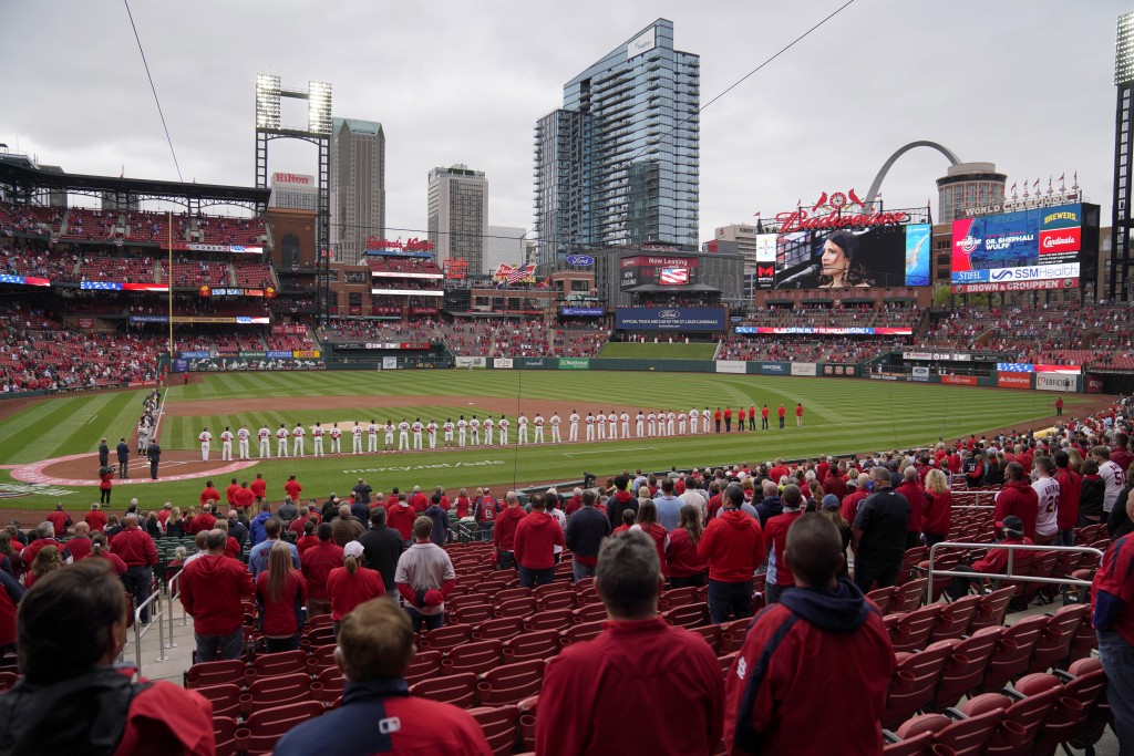 Fans stand along with members of the St. Louis Cardinals and Milwaukee Brewers for the singing of the Star Spangled Banner before the start of a baseb...