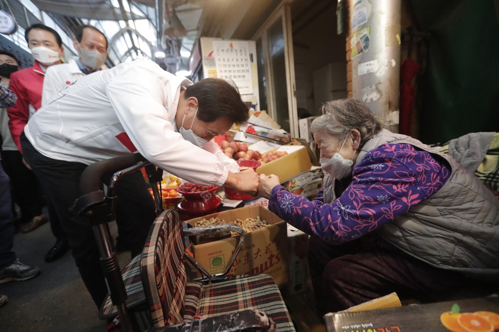 Oh Se-hoon, left, the candidate of the main opposition People Power Party, bumps fists with a vendor during a campaign for the April 7 Seoul mayoral b...
