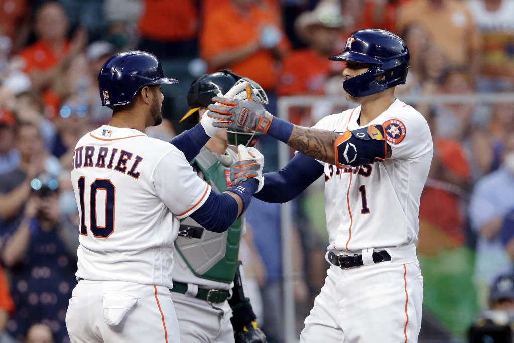 Houston Astros' Yuli Gurriel (10) and Carlos Correa (1) celebrate at the plate after Correa's home run during the second inning against the Oakland At...