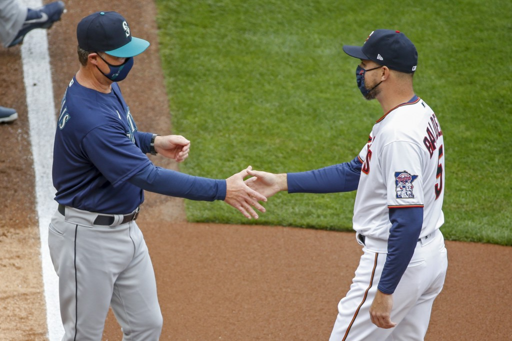 Seattle Mariners manager Scott Servais greets Minnesota Twins manager Rocco Baldelli during the introductions at the home opener baseball game Thursda...