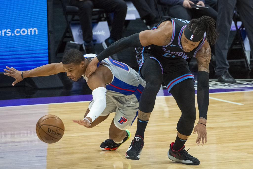Detroit Pistons guard Dennis Smith Jr. (0) and Sacramento Kings center Richaun Holmes chase the ball during the first quarter of an NBA basketball gam...