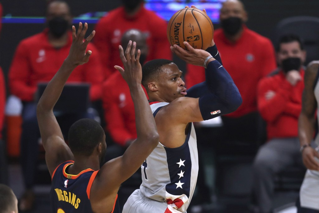 Washington Wizards guard Russell Westbrook shoots next to Golden State Warriors forward Andrew Wiggins during the first half of an NBA basketball game...