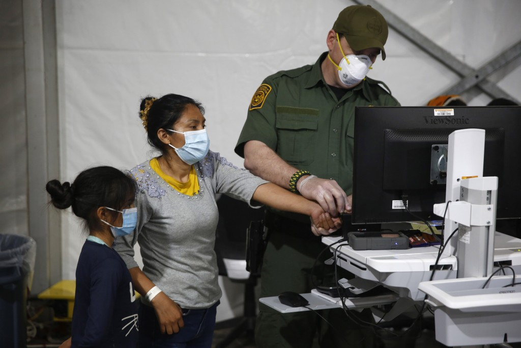 FILE - In this March 30, 2021, file photo, a migrant and her daughter have their biometric data entered at the intake area of the U.S. Department of H...