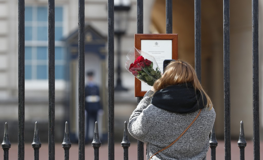 A woman reads the official death notice of Britain's Prince Philip as she prepares to lay flowers at the gate of Buckingham Palace in London, Friday, ...