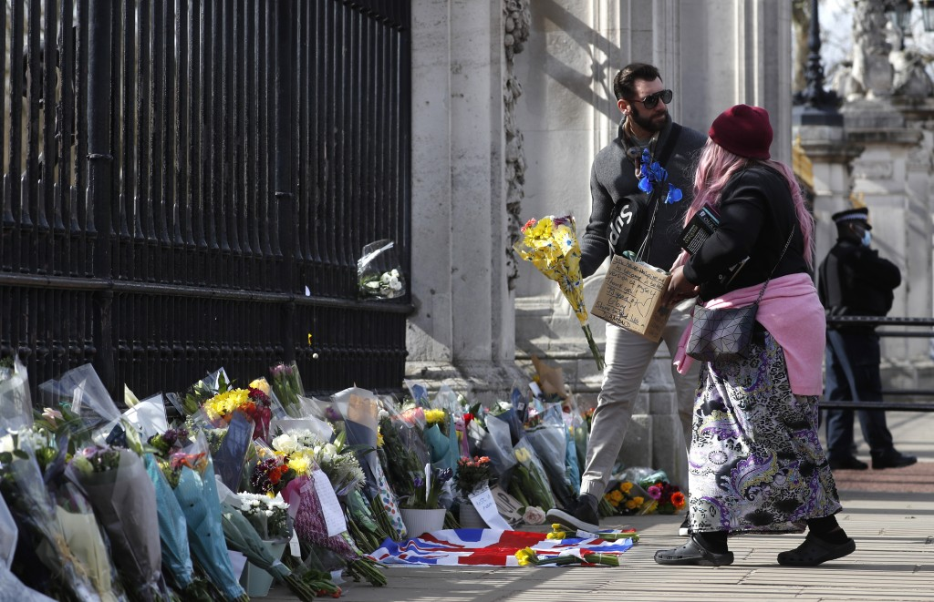 A woman prepares to lay a bouquet of flowers in a box with a message near the front of the gate at Buckingham Palace in London, Friday, April 9, 2021....