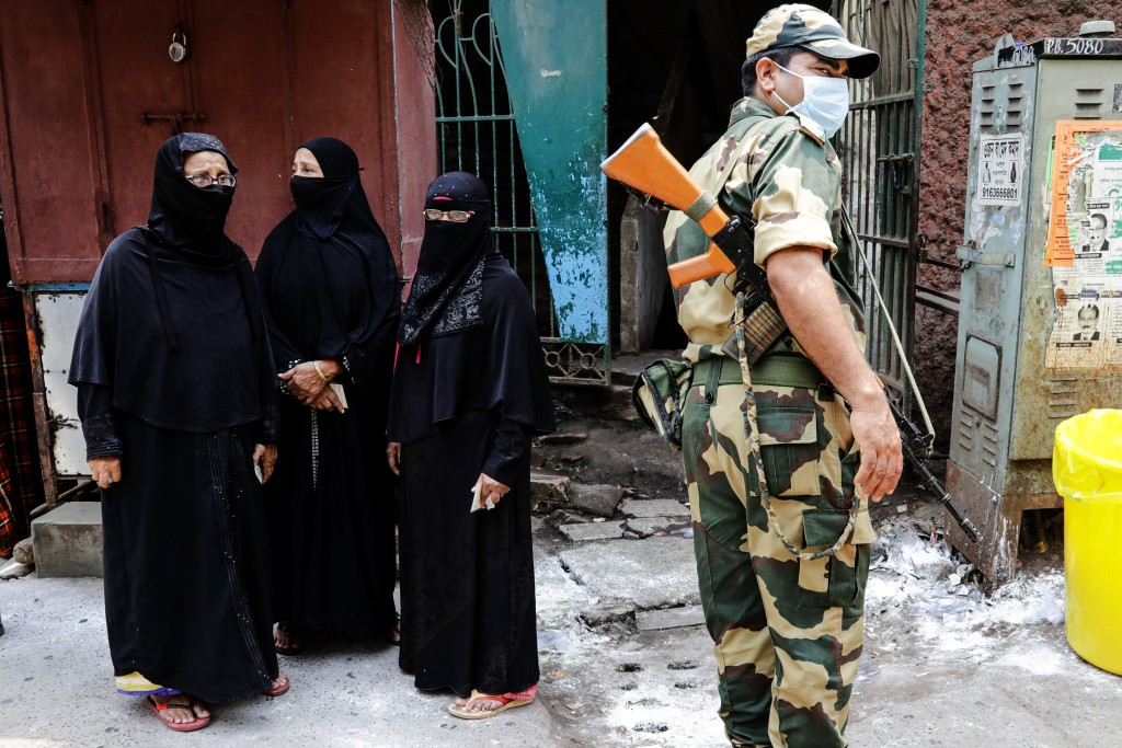 A paramilitary soldier stands guards as voters wait to cast their votes at a polling station during the fourth phase of West Bengal state elections in...
