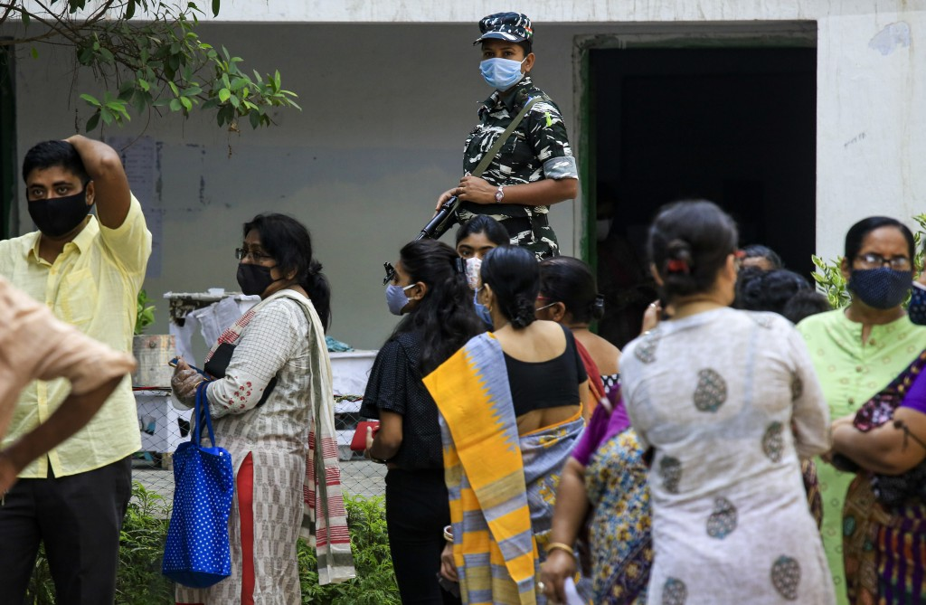 A paramilitary solder stands vigil as people stand in a queue to cast their votes outside a polling station during the fourth phase of West Bengal sta...
