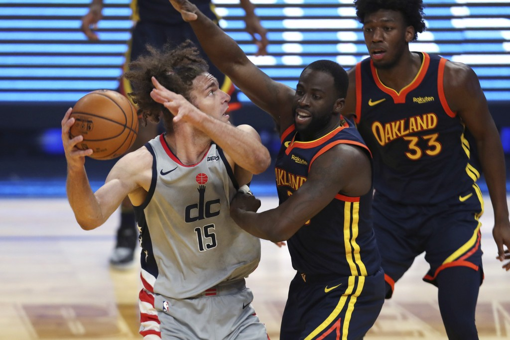 Washington Wizards center Robin Lopez, left, looks for a shot against Golden State Warriors forward Draymond Green during the first half of an NBA bas...