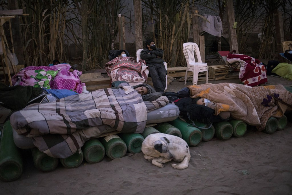 People sleep on top of empty oxygen cylinders, waiting for a shop to open in order to refill their tanks, in the Villa El Salvador neighborhood, as a ...