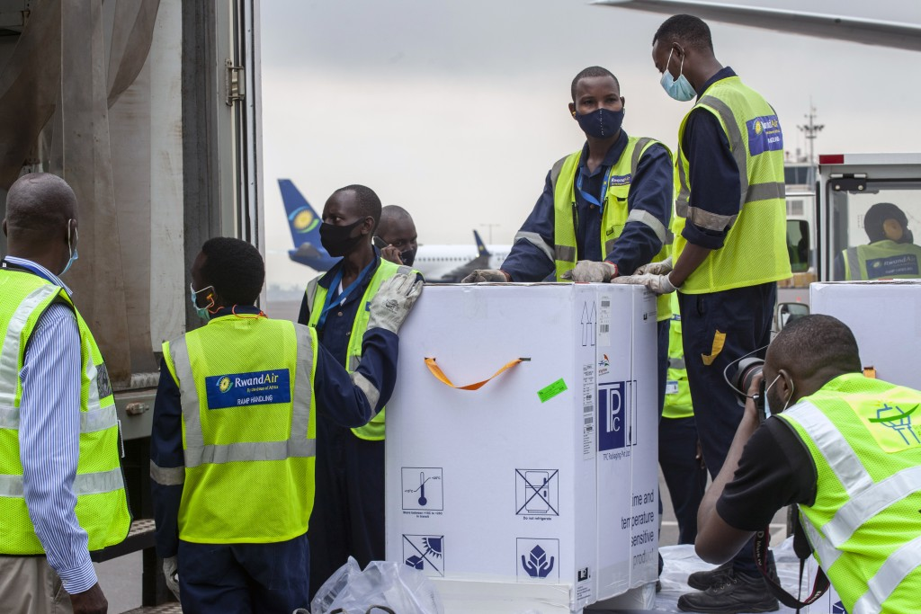 FILE - In this March 3, 2021, file photo, AstraZeneca COVID-19 vaccines are received by airport workers at the airport in Kigali, Rwanda. The COVAX gl...