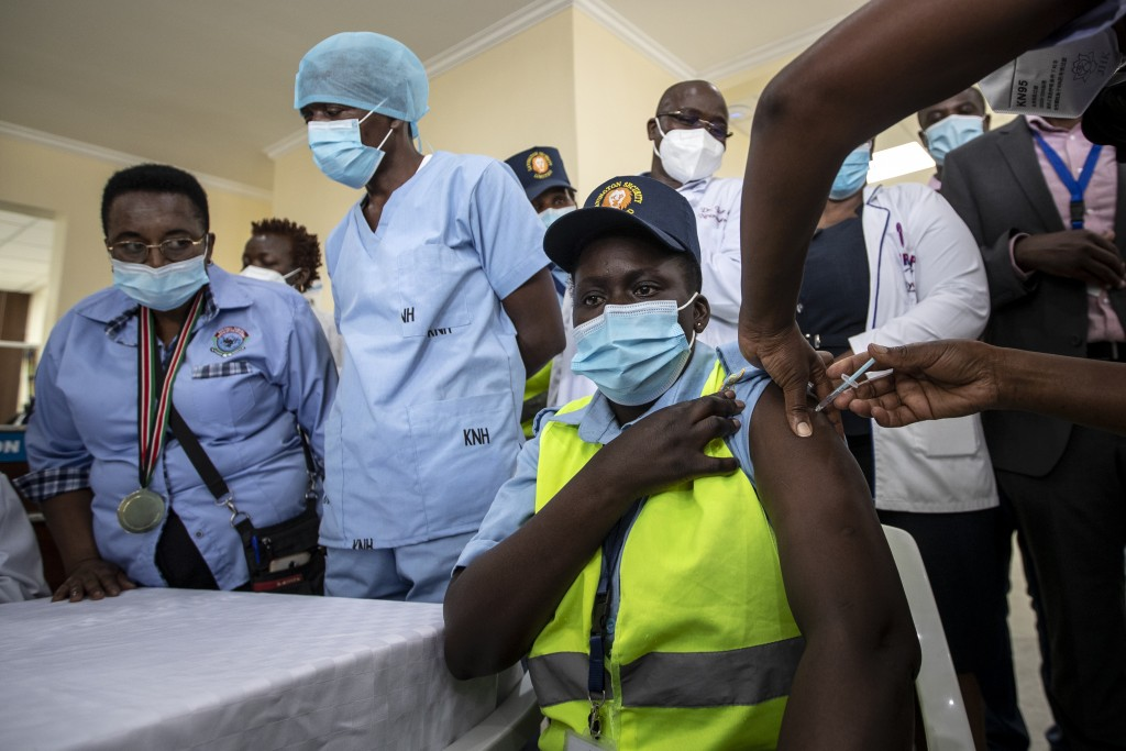 FILE - In this March 5, 2021, file photo, a hospital security guard receives one of Kenya's first AstraZeneca COVID-19 vaccinations provided through t...