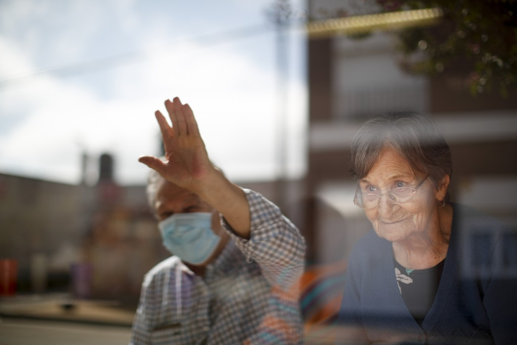 Arceli Armando watches her son wave to her from outside of the Reminiscencias residence for the elderly where she lives in Tandil, Argentina, Monday, ...