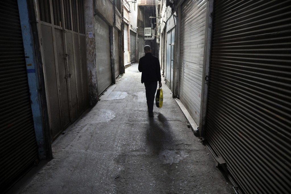 A man walks through closed Tehran's Grand Bazaar, Iran, Saturday, April 10, 2021. Iran on Saturday imposed partial lockdown on businesses in major sho...