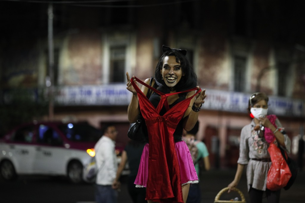 Sex worker Geraldine, wearing cat make-up, excitedly holds up a dress she is thinking of buying from a street vendor, so that her partner, sitting nea...