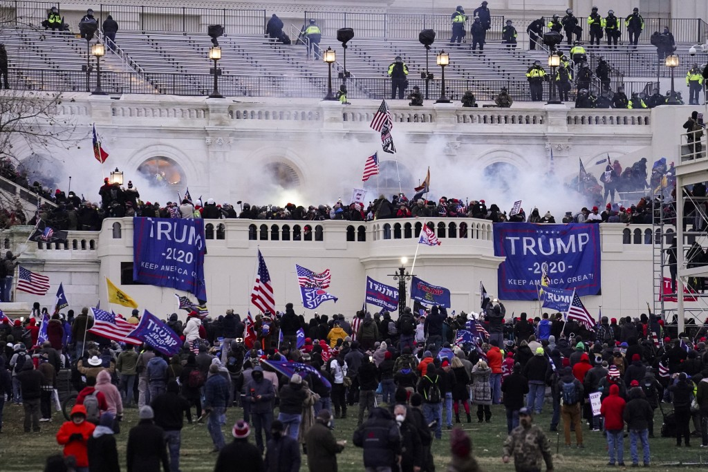 FILE - In this Wednesday, Jan. 6, 2021, file photo, violent rioters storm the Capitol, in Washington. New details from the deadly riot of Jan. 6 are c...