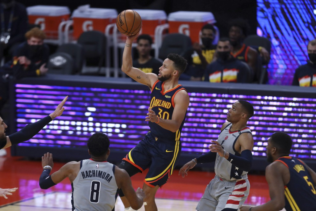 Golden State Warriors guard Stephen Curry, center, shoots against Washington Wizards forward Rui Hachimura, left, and guard Russell Westbrook, right, ...