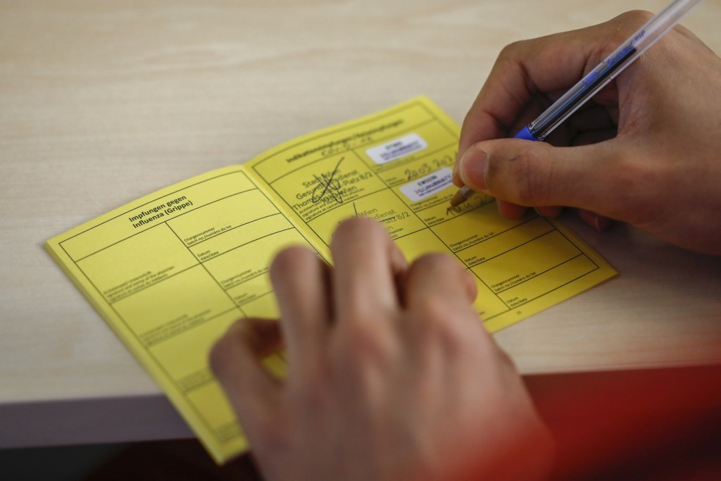 A health worker puts his signature in the vaccination pass of the patient Kurt Switil at the vaccination center 'Am Schoepfwerk' in Vienna, Austria, S...