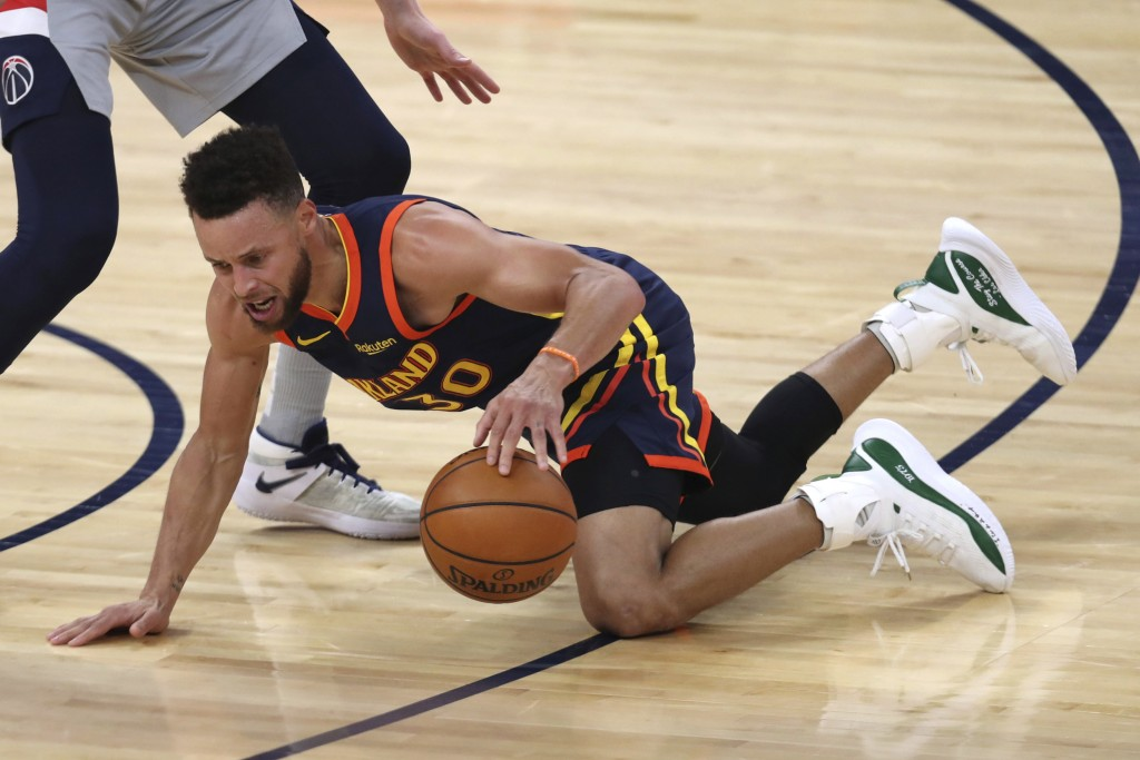 Golden State Warriors guard Stephen Curry dribbles after falling down during the first half of the team's NBA basketball game against the Washington W...