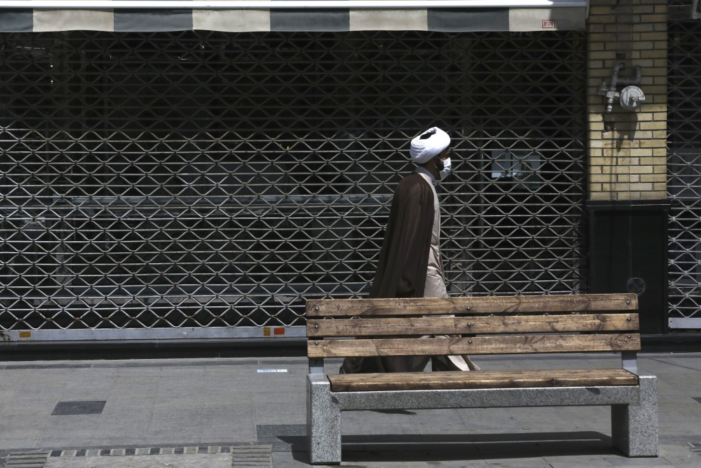 A cleric walks past a closed shop of Tehran's Grand Bazaar, Iran, Saturday, April 10, 2021. Iran on Saturday imposed partial lockdown on businesses in...