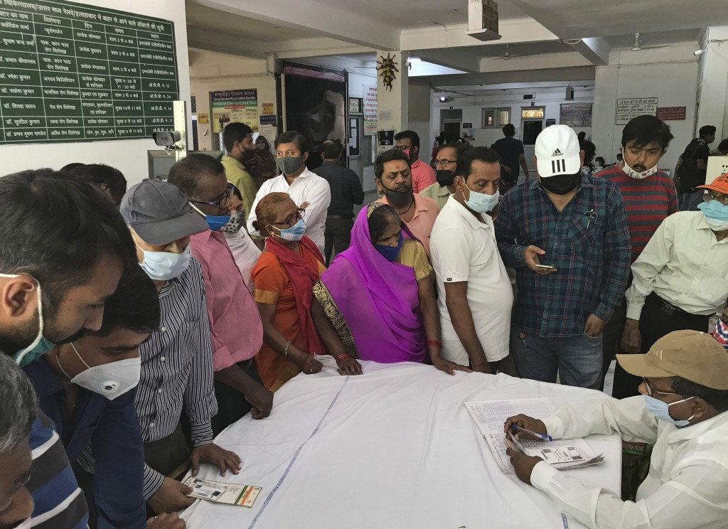 People wait to register themselves to receive the vaccine for COVID-19 at Railway hospital in Prayagraj, India, Saturday, April 10, 2021. India has a ...