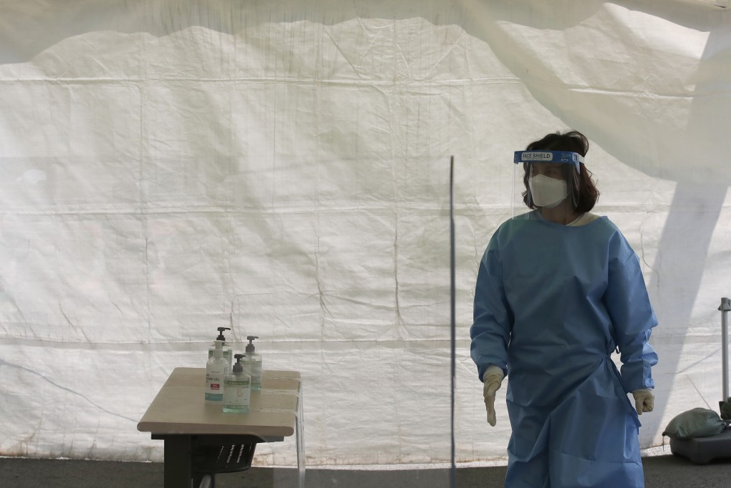 A health official wearing protective suits tries to help visitors at a temporary screening clinic for coronavirus in Seoul, South Korea, Saturday, Apr...