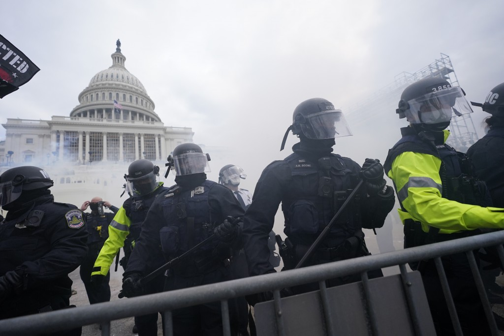 FILE - In this Jan. 6, 2021, file photo, police stand guard after holding off violent rioters who tried to break through a police barrier at the Capit...
