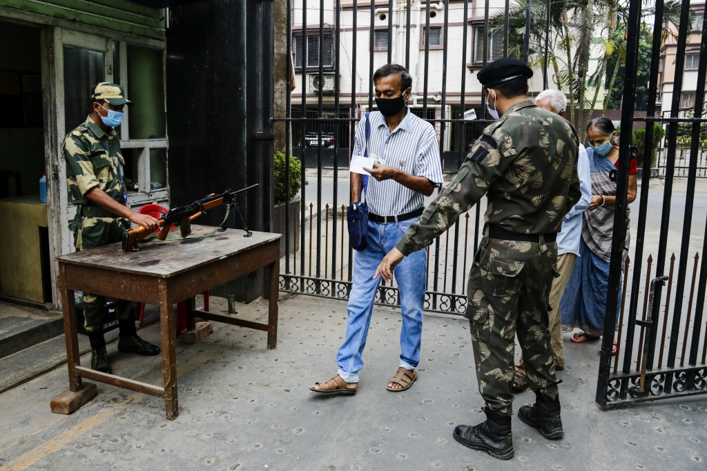 Paramilitary soldiers keep vigil as voters enter a polling station during the fourth phase of West Bengal state elections in Kolkata, India, Saturday,...