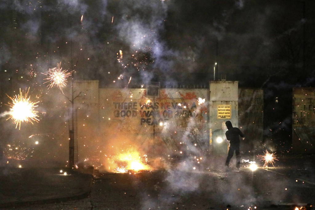 Fireworks explode as Nationalist and Loyalist rioters clash with one another at the peace wall on Lanark Way in West Belfast, Northern Ireland, Wednes...