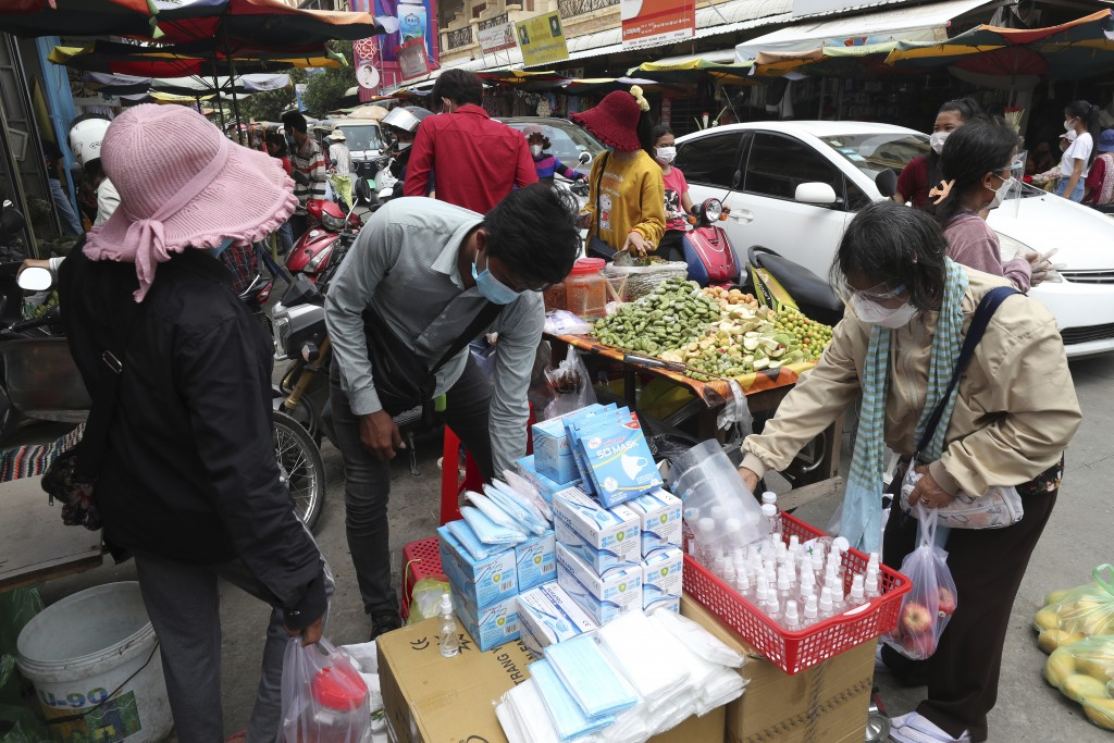 A customer, right, wears a protective face mask to prevent the spread of the coronavirus, buys items at a local market outside Phnom Penh, Cambodia, S...
