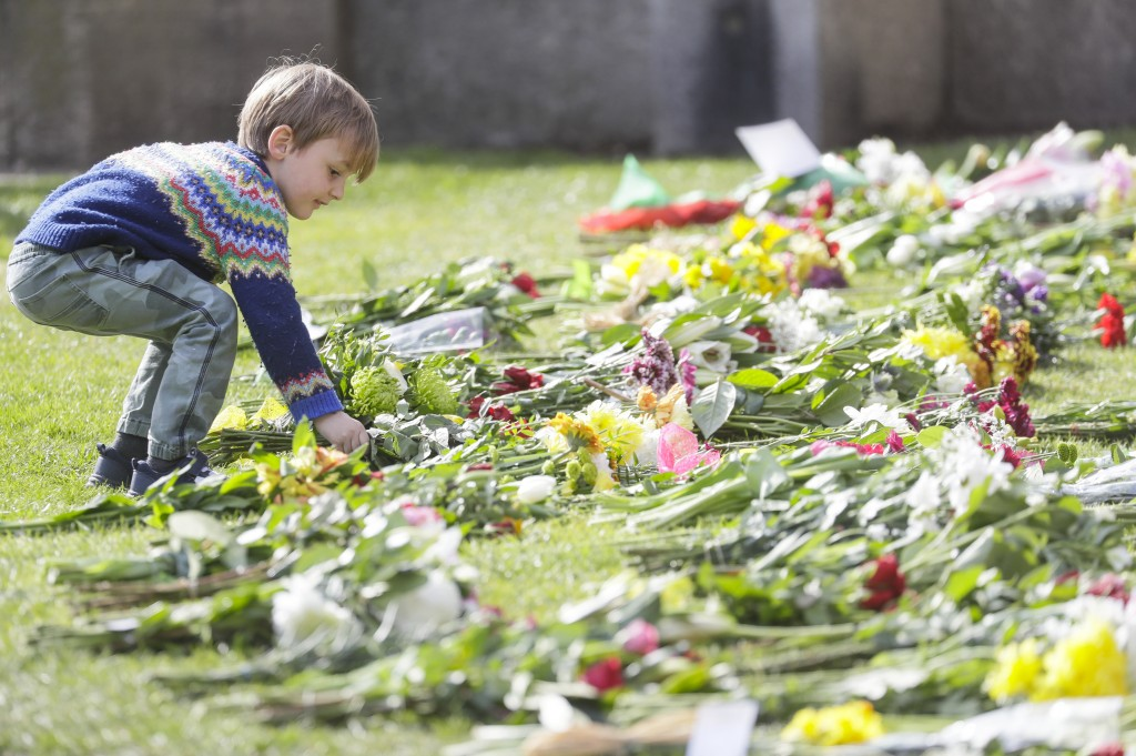 A child lays flowers outside the Cambridge gate of Windsor Castle in Windsor, England after the announcement regarding the death of Britain's Prince P...