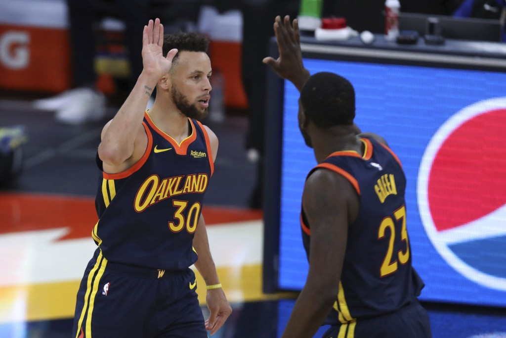 Golden State Warriors guard Stephen Curry is congratulated by Draymond Green after making a basket against the Houston Rockets during the second half ...