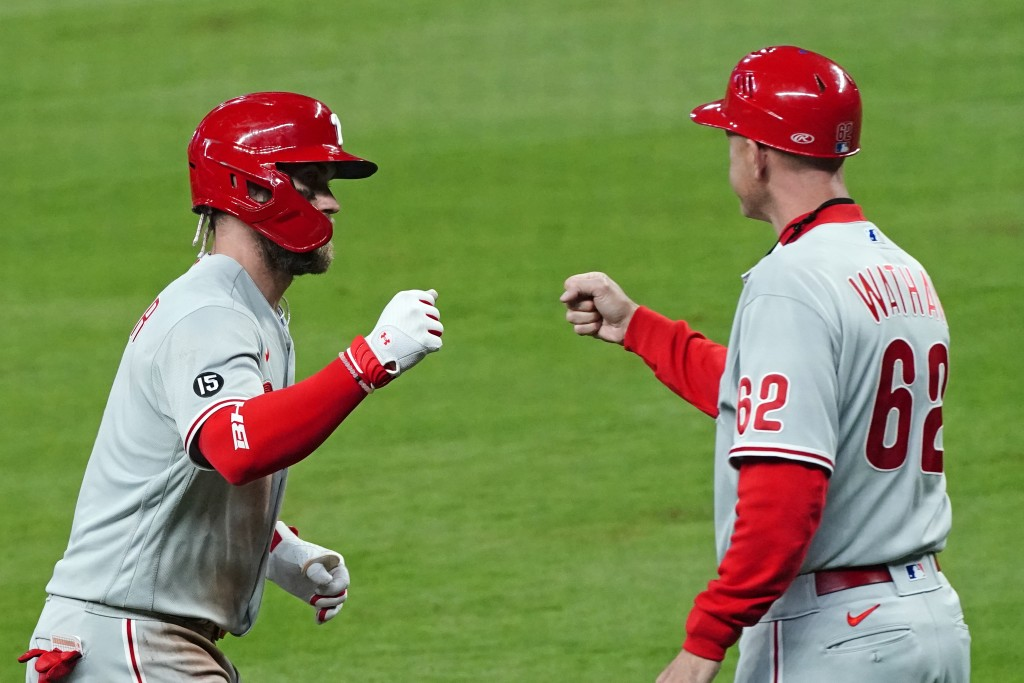 Philadelphia Phillies' Bryce Harper (3) celebrates with third base coach Dusty Wathan (62) as he rounds third base after hitting a home run in the six...