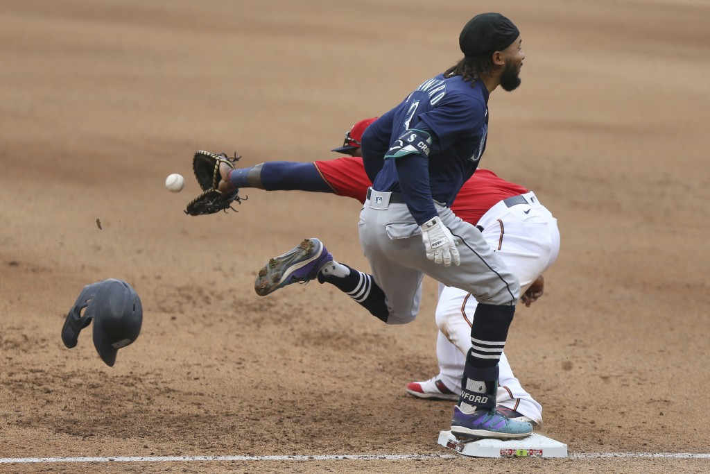 Seattle Mariners' J.P. Crawford (3) best the throw to first base as Minnesota Twins' Miguel Sano (22) reaches for he ball during the eighth inning of ...