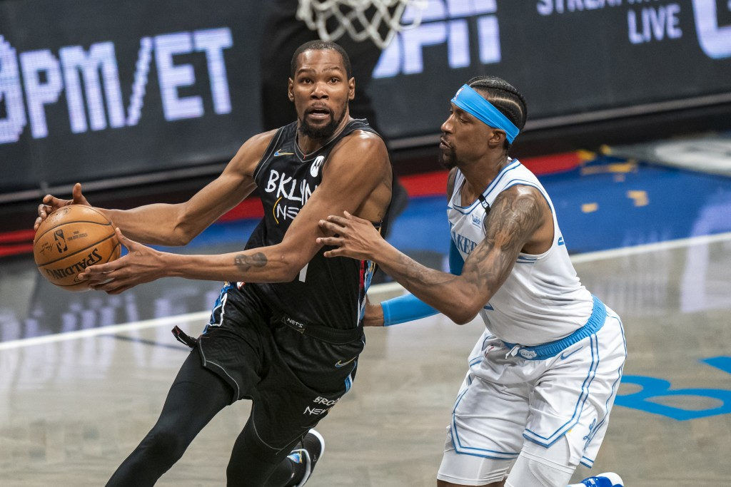 Brooklyn Nets forward Kevin Durant drives past Los Angeles Lakers guard Kentavious Caldwell-Pope in the first half of an NBA basketball game, Saturday...