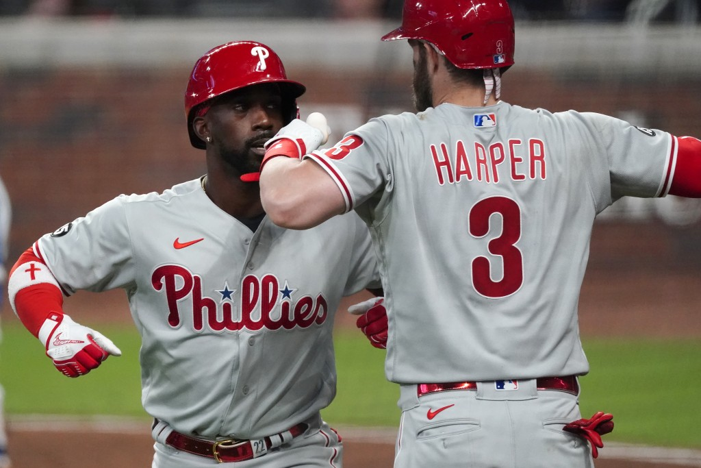 Philadelphia Phillies' Andrew McCutchen (22) celebrates with Bryce Harper (3) after hitting a solo home run in the fifth inning of a baseball game aga...