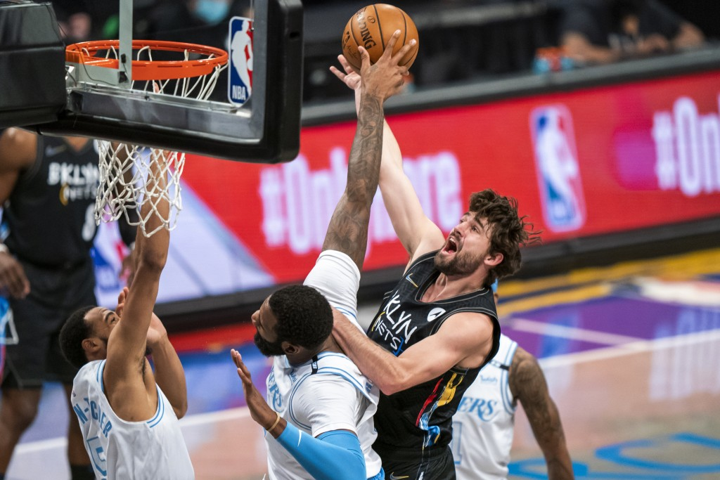 Los Angeles Lakers center Andre Drummond defends against Brooklyn Nets forward Joe Harris, top, during the first half of an NBA basketball game, Satur...