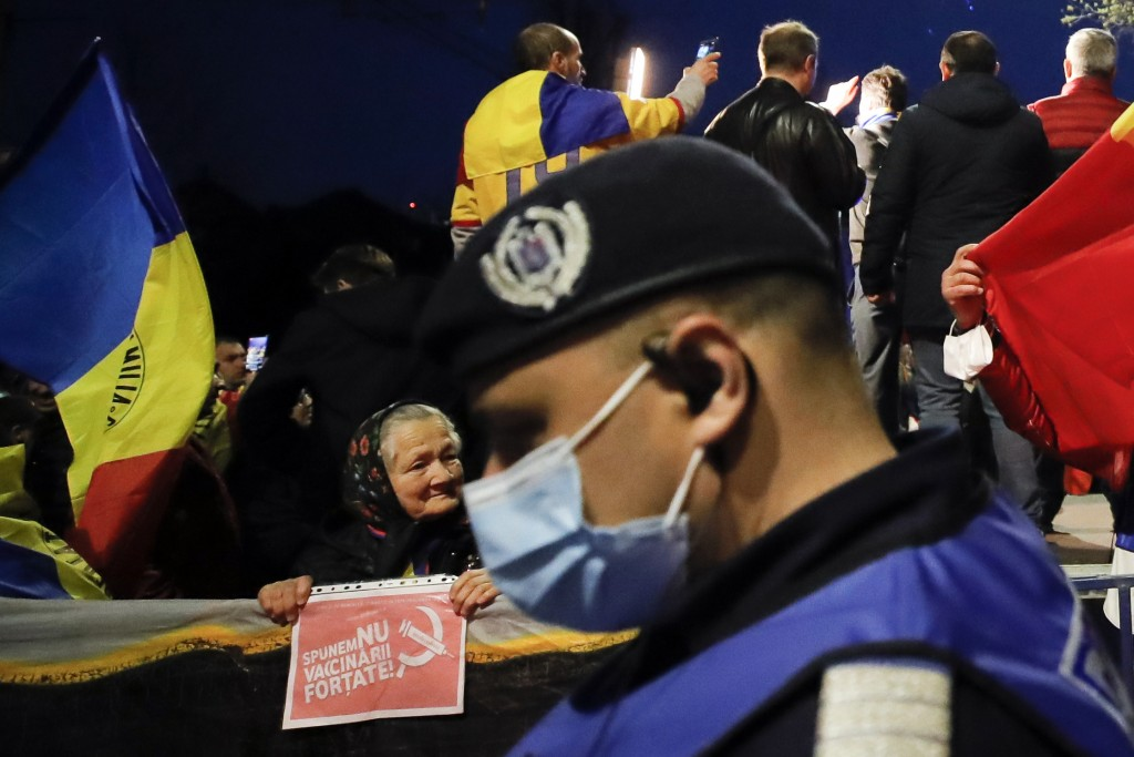 """An elderly woman holds a paper that reads """"We say no to forced vaccination"""" during a protest outside the Cotroceni Presidential Palace in Bucharest, R..."""