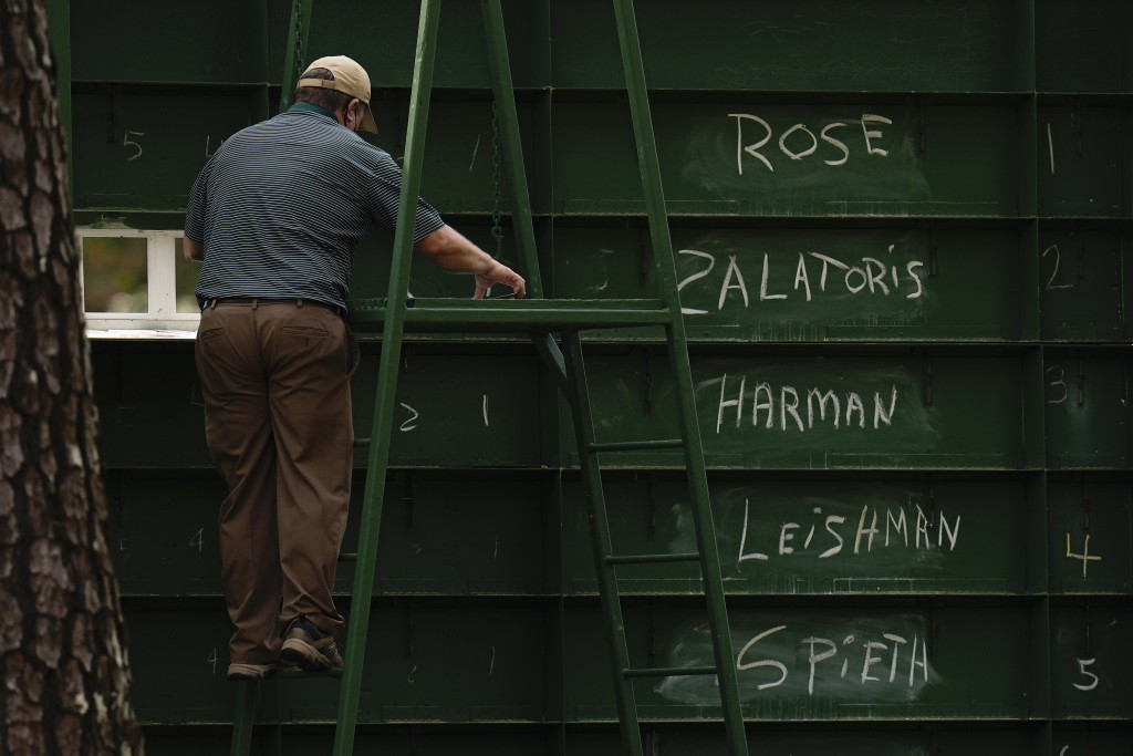 An attendant adjusts the scores of golfers from behind a leaderboard during the third round of the Masters golf tournament on Saturday, April 10, 2021...