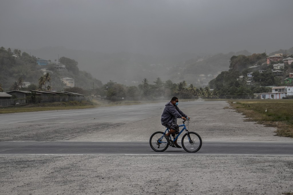 A man rides his bicycle past fields covered with volcanic ash a day after the La Soufriere volcano erupted, in Kingstown, on the eastern Caribbean isl...