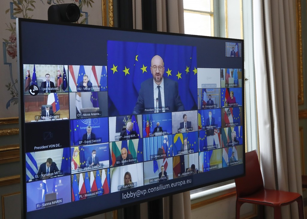 FILE - In this March 25, 2021, file photo, European Council President Charles Michel shown on a screen, center, speaks during a video conference of a ...