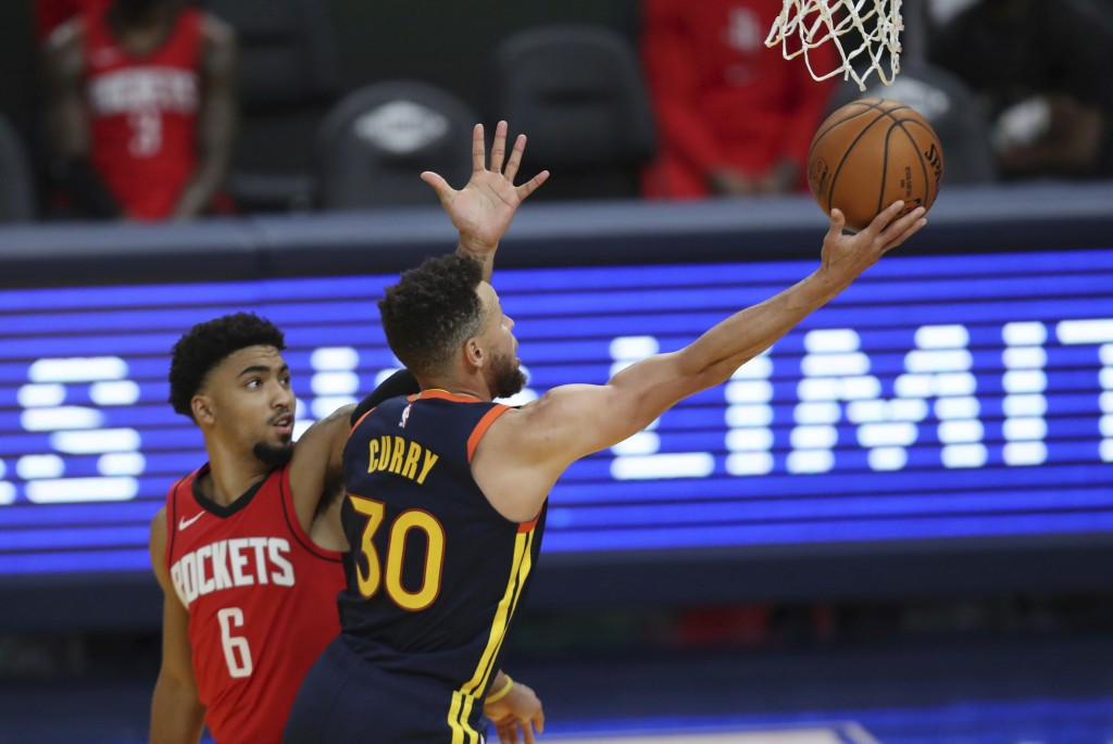 Golden State Warriors guard Stephen Curry shoots next to Houston Rockets guard KJ Martin during the second half of an NBA basketball game in San Franc...