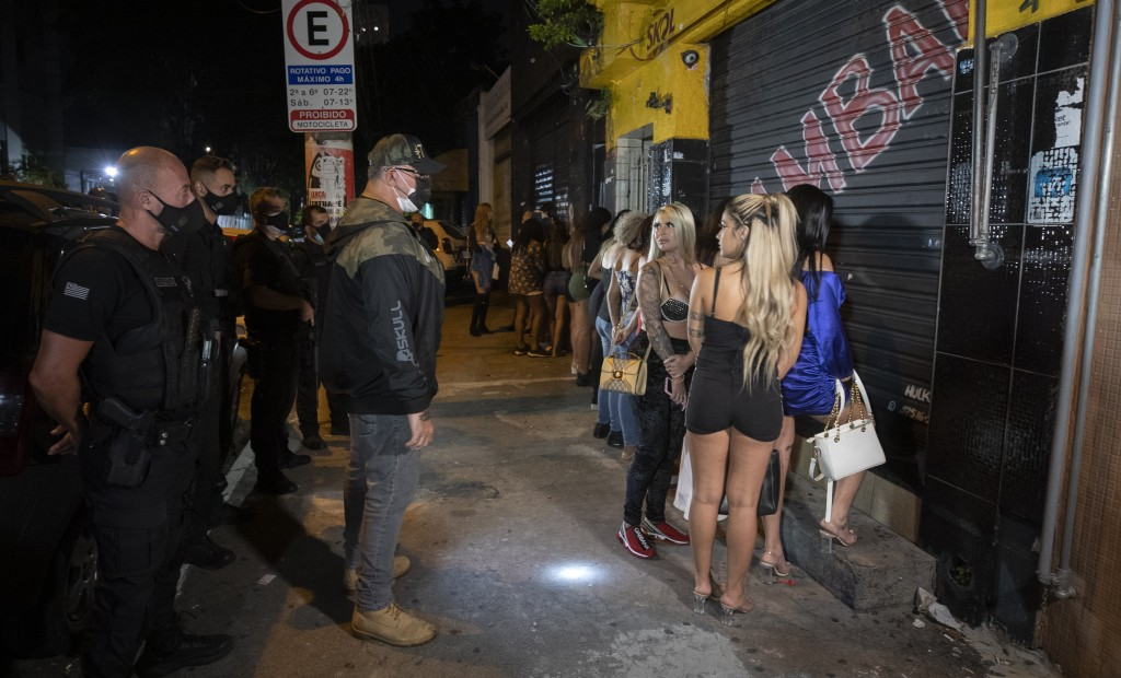 A policeman talks with a woman outside a night club after it was shut down during a police operation against illegal and clandestine gatherings that a...