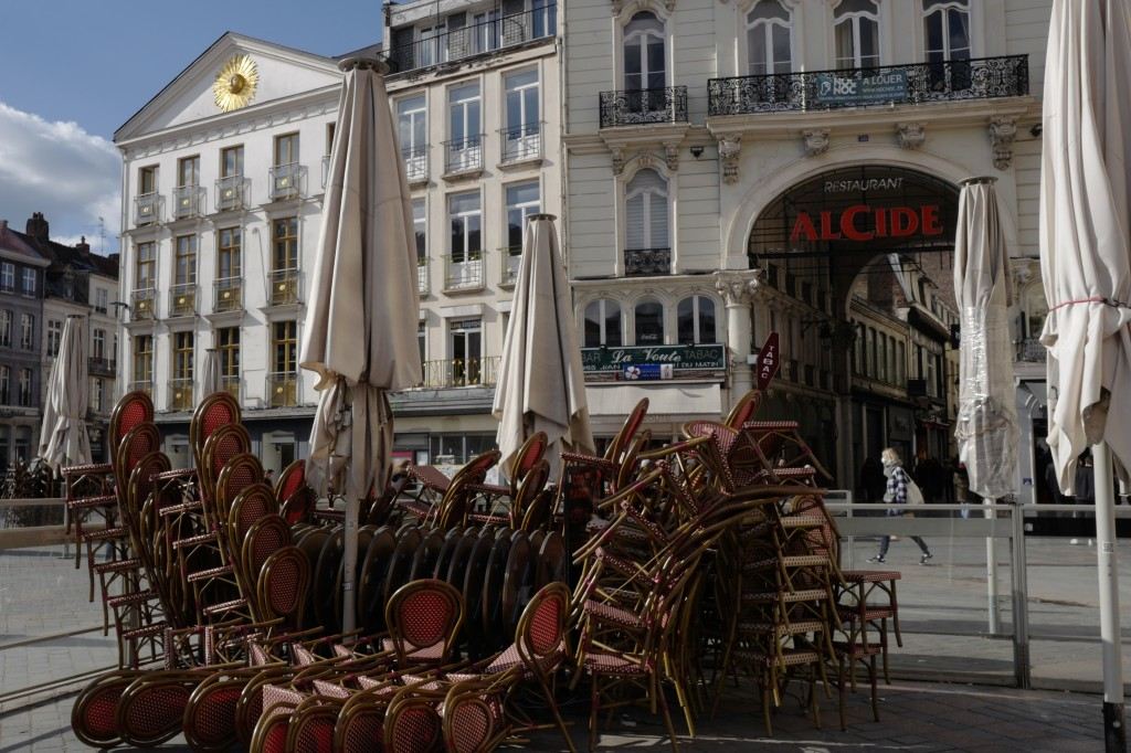 FILE - In this March 19, 2021, file photo, stacked chairs in front of a cafe during the coronavirus pandemic in Lille, northern France. Lofty hopes th...