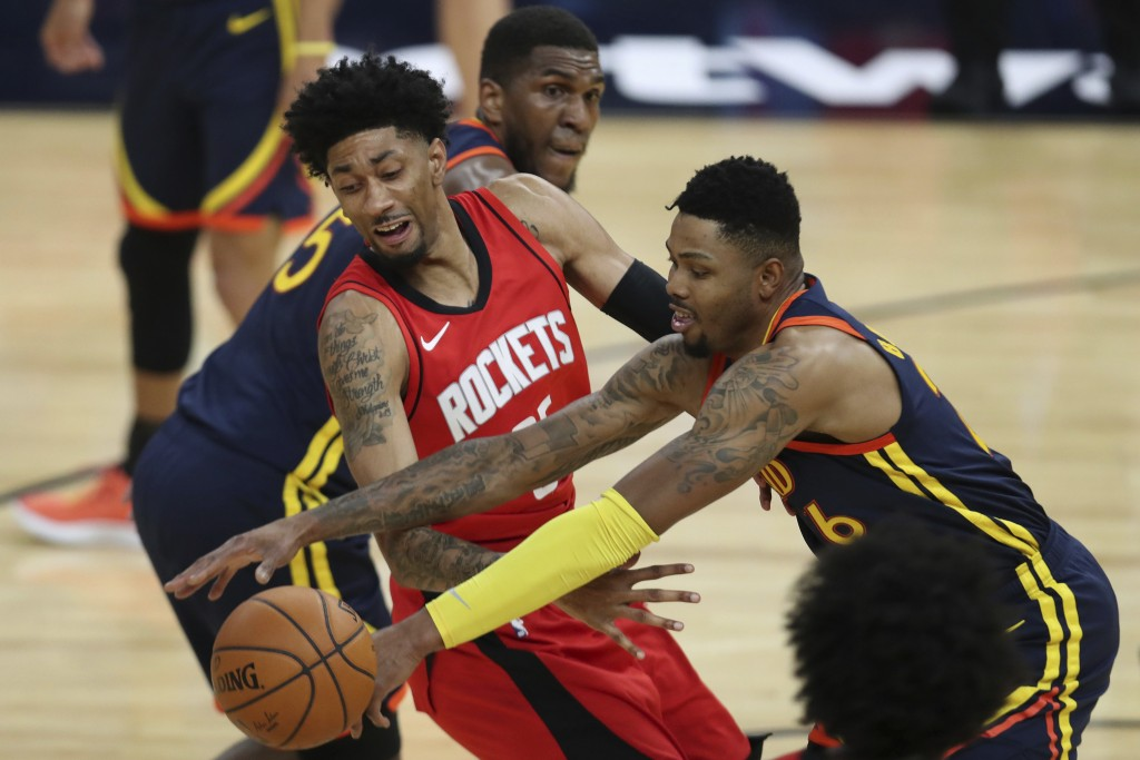 Golden State Warriors guard Kent Bazemore, right, reaches for the ball next to Houston Rockets forward Christian Wood during the first half of an NBA ...