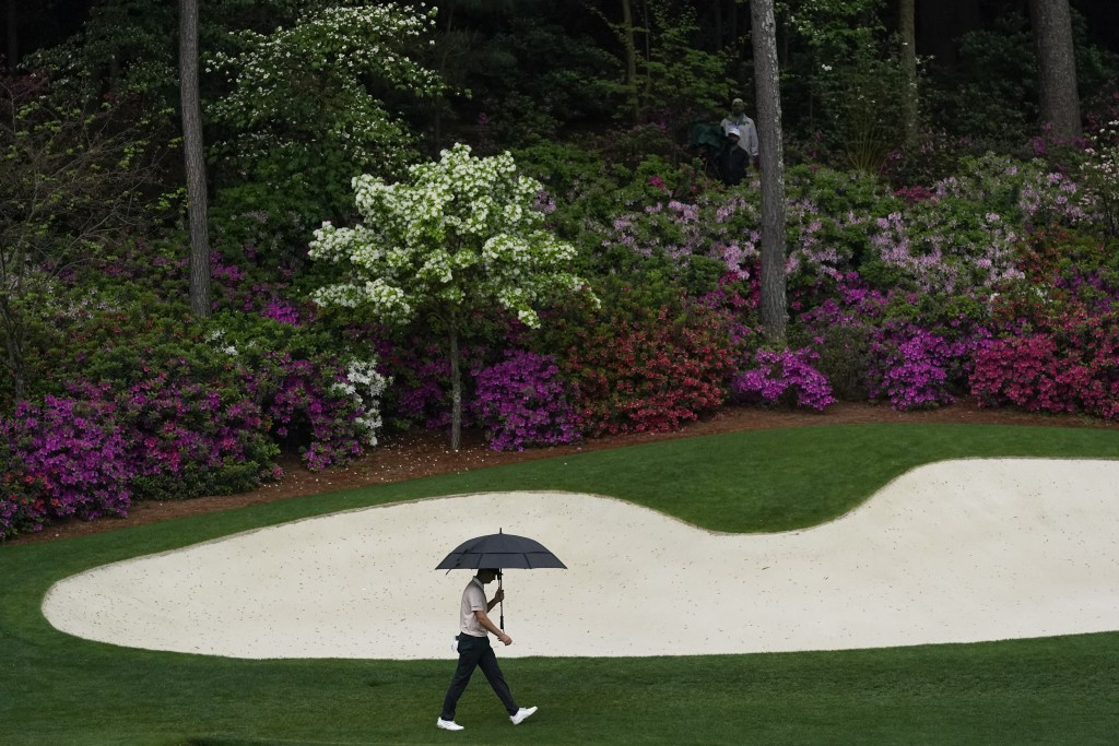 Justin Rose, of England, walks in the rain to the 13th green during the third round of the Masters golf tournament on Saturday, April 10, 2021, in Aug...
